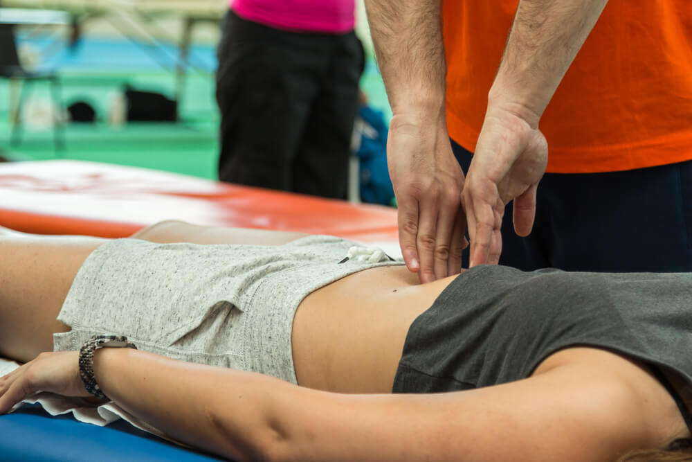 male masseuse pointing finger into athletes stomach