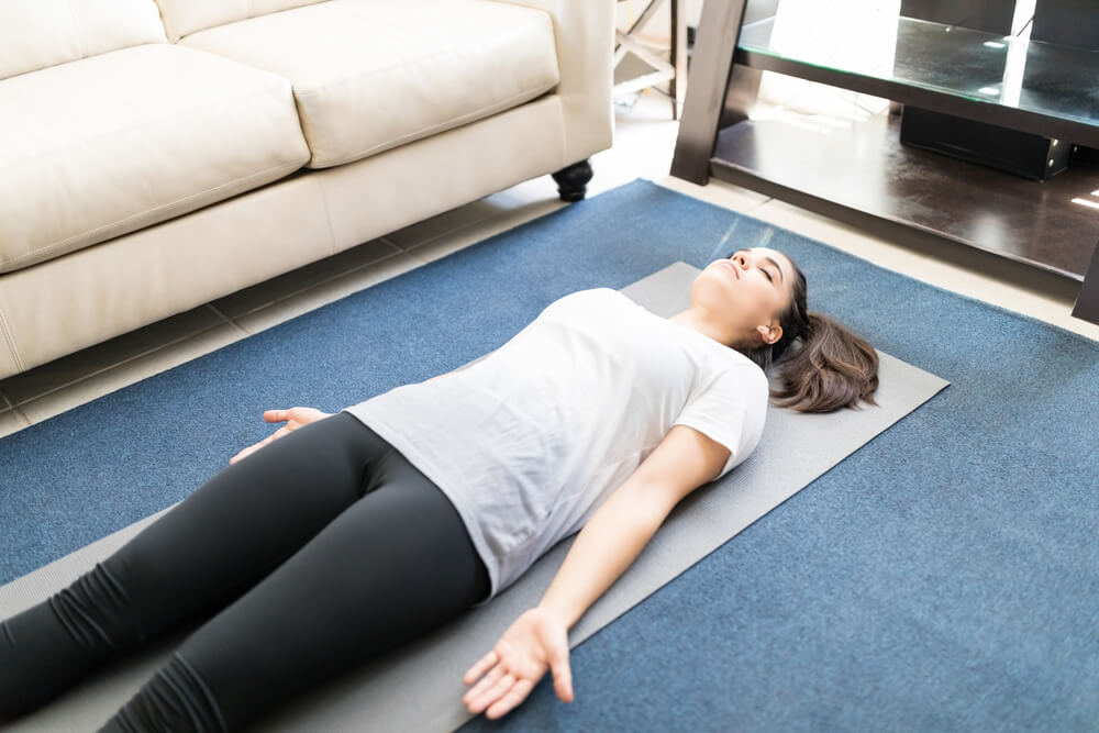 girl lying down doing a body scan meditation