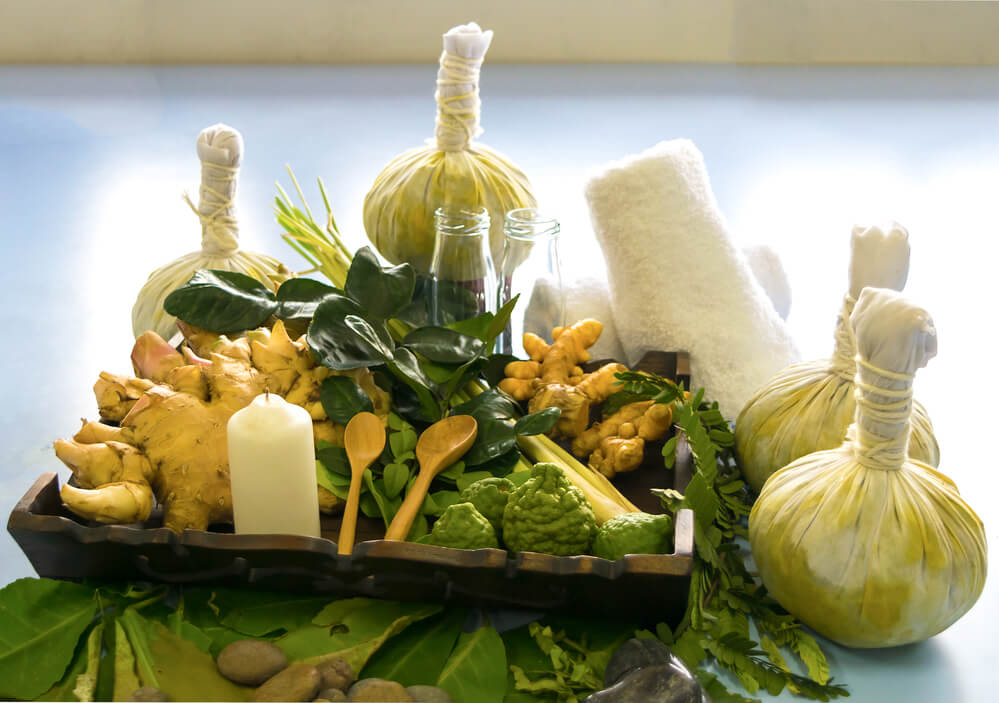 Four Thai Herbal Compress Balls Beside The Ingredients And A White Towel