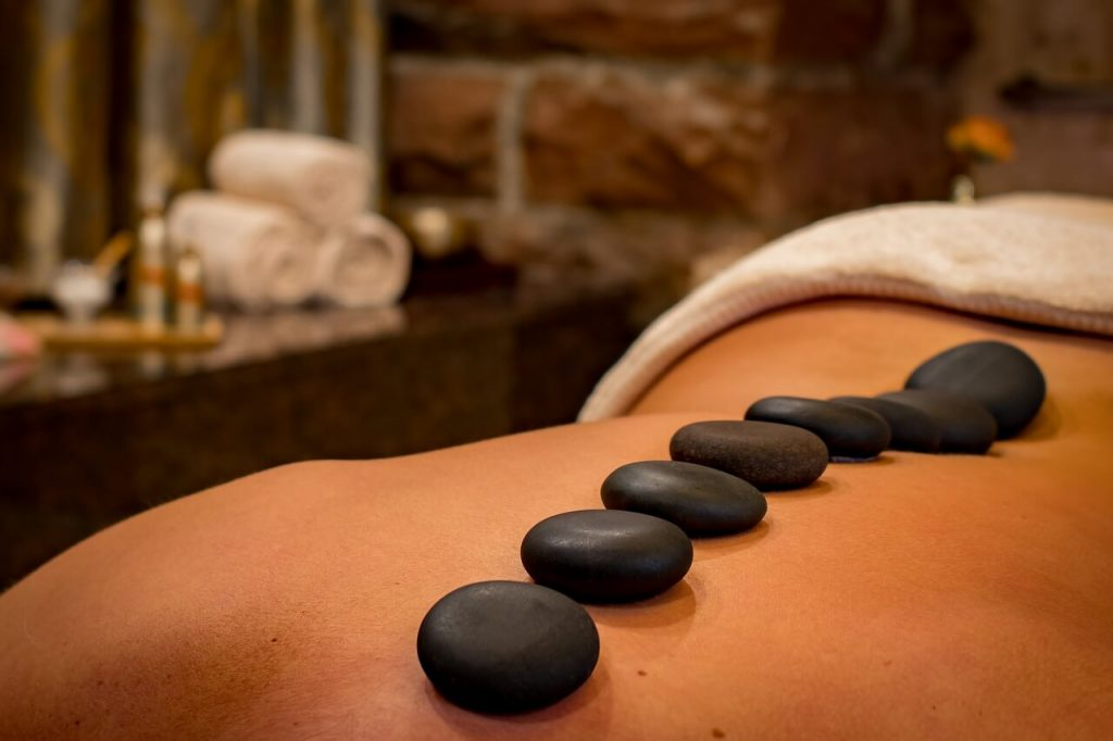 eight hot basalt massage stones on the back of a client