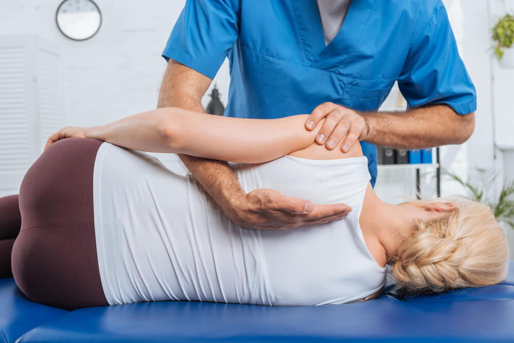 chiropractor in blue uniform working on a patient
