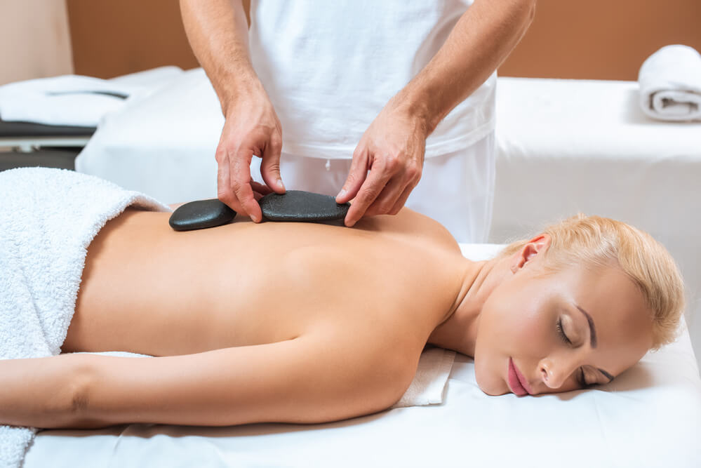 blonde woman getting a hot stone massage on her back