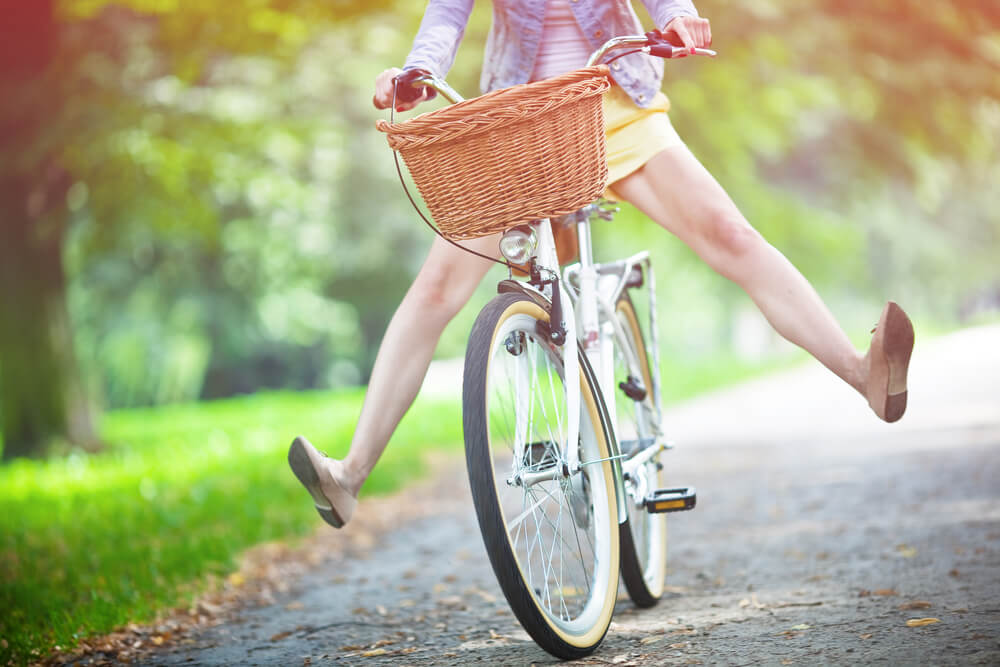happy woman riding a bike down a path