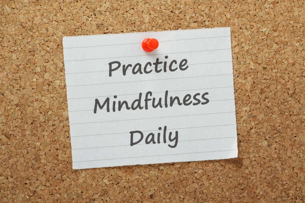 note on a corkboard that says practice mindfulness daily